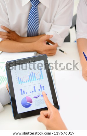 Close-up of businessman pointing at financial document in touchpad - stock photo