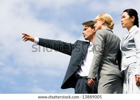 Close-up of businessman pointing at something while two elegant ladies looking at it - stock photo
