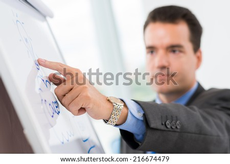 Close-up of businessman pointing at the bulb on the flipchart as a symbol of new idea - stock photo