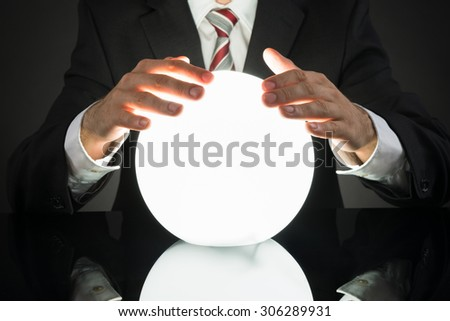 Close-up Of Businessman Predicting Future With Crystal Ball At Desk - stock photo
