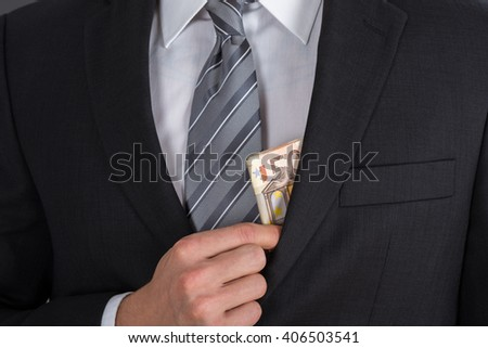 Close-up Of Businessman Putting Bribe Money In Suit Pocket - stock photo