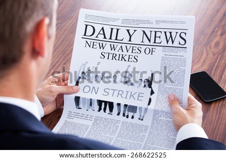 Close-up Of Businessman Reading News On Newspaper - stock photo