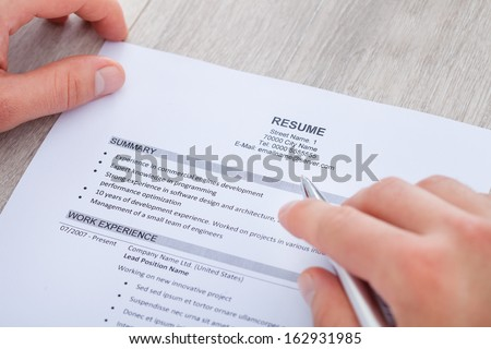 Close-up Of Businessman Reading Resume With Tea Cup On Desk - stock photo