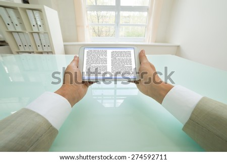 Close-up Of Businessman Reading Text On Digital Tablet Screen. Book page Contains Placeholder Text - stock photo