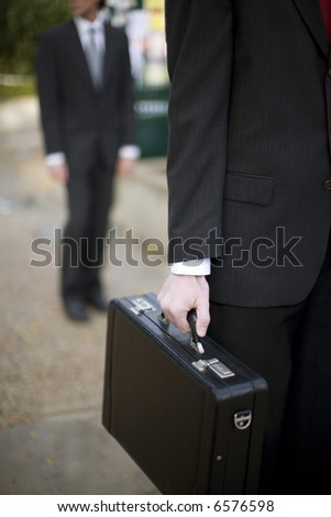 close up of businessman's hand holding briefcase with another businessman standing in background