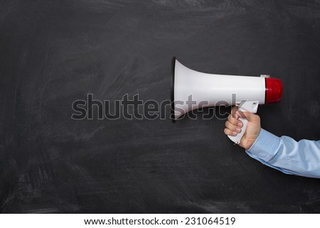 Close up of businessman's hand holding megaphone over chalkboard background with copy space - stock photo