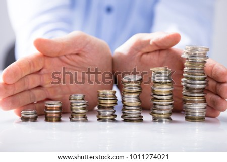 Close-up Of Businessman's Hand Protecting The Increasing Stack Of Coins On White Desk