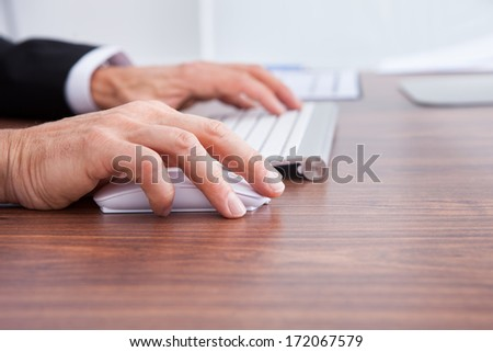 Close-up Of Businessman's Hand Using Computer At Desk - stock photo
