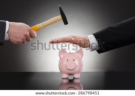 Close-up Of Businessman's Hands Saving Piggybank From Hammering - stock photo