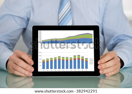 Close-up Of Businessman Showing Graph On Digital Tablet