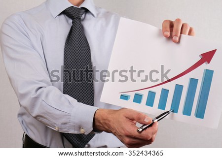 Close up of businessman showing  rising arrow, representing business growth. Manager showing presentation of progressive arrow chart. Success, team work, leadership concept