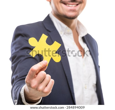 Close-up of businessman showing small jigsaw puzzle over white background. - stock photo