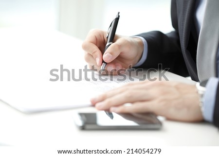 Close-up of businessman signing a contract - stock photo
