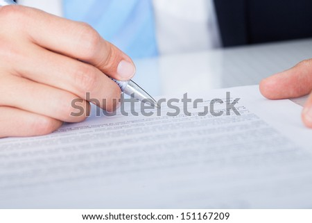 Close-up Of Businessman Signing Contract Paper With Pen - stock photo