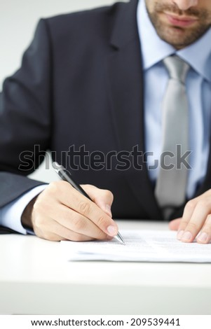 Close-up of businessman sitting at office and fill the form. Business people.