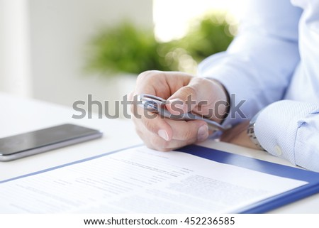 Close-up of businessman sitting at office desk and signing the contract.