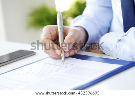 Close-up of businessman sitting at office desk and signing the contract.  - stock photo