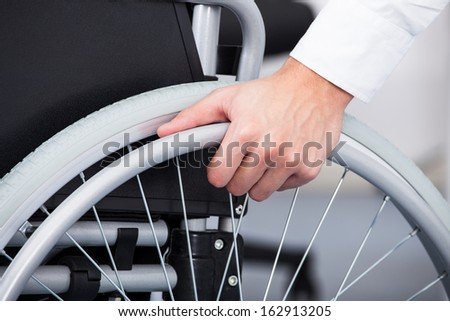 Close-up Of Businessman Sitting On Wheelchair In Office - stock photo