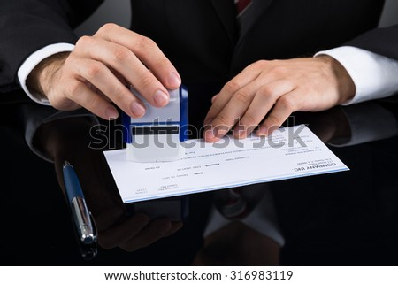 Close-up Of Businessman Stamping Cheque At Desk - stock photo