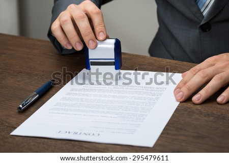 Close-up Of Businessman Stamping Document At Desk In Office
