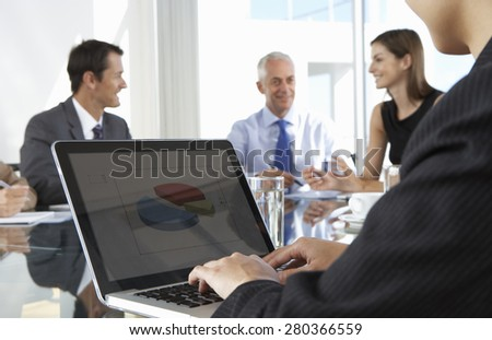 Close Up Of Businessman Using Laptop During Board Meeting Around Glass Table - stock photo