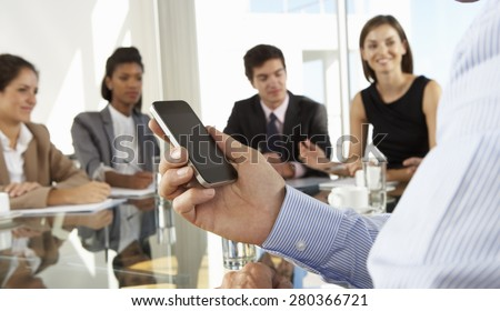 Close Up Of Businessman Using Mobile Phone During Board Meeting Around Glass Table - stock photo
