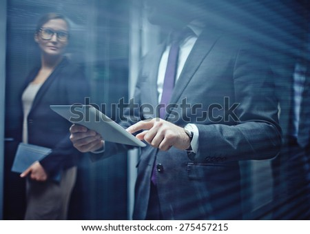 Close-up of businessman using touchpad on background of woman - stock photo