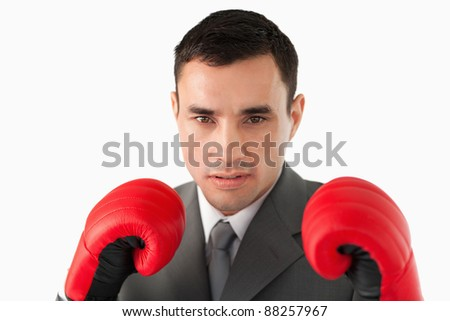Close up of businessman wearing boxing gloves against a white background