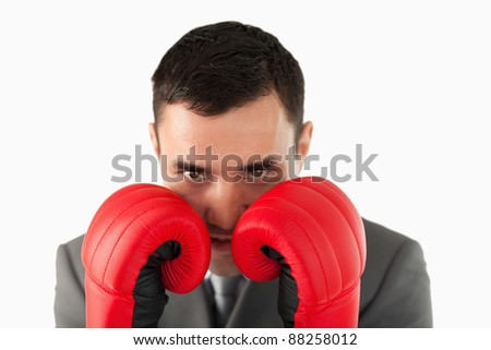 Close up of businessman with boxing gloves taking cover against a white background