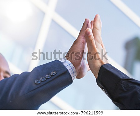 Close-up of businessmen giving each other high five. Agreement concept.