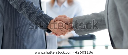 Close-up of businessmen shaking hands in an office - stock photo