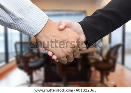 Close up of businessmen shaking hands in meeting room. - stock photo
