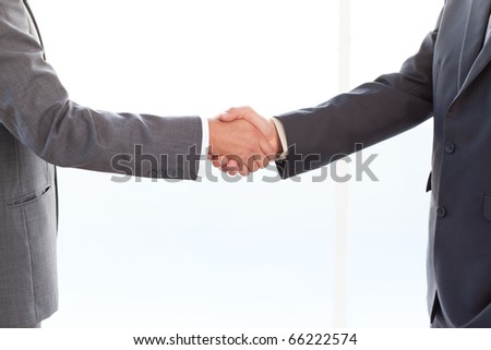 close up of businessmen shaking their hands after a meeting at the office - stock photo