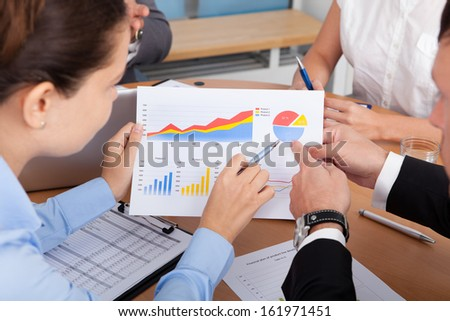 Close-up Of Businesspeople Analyzing Graph Together In Office - stock photo