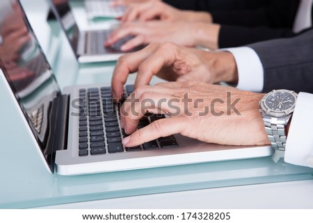 Close-up Of Businesspeople Hand's Typing On Laptop - stock photo