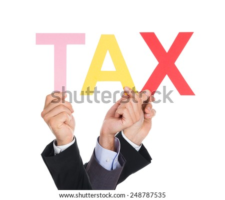 Close-up Of Businesspeople Hands Holding Text Tax - stock photo