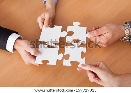 Close-up Of Businesspeople Holding Jigsaw Puzzle Over Desk - stock photo