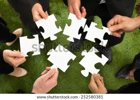 Close-up Of Businesspeople Holding White Jigsaw Puzzle In Hand - stock photo