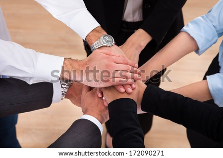 Close-up Of Businesspeople Putting Their Hands On Top Of Each Other - stock photo
