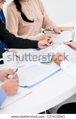 Close-up of businesspeople's hands working with printed documents - stock photo