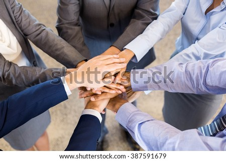 Close-up of Businesspeople stacking hands in meeting at office - stock photo