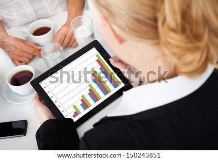 Close-up Of Businessperson Analyzing Business Graph On Digital Tablet - stock photo