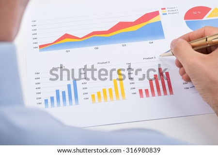 Close-up Of Businessperson Analyzing Colorful Graphs On Paper - stock photo