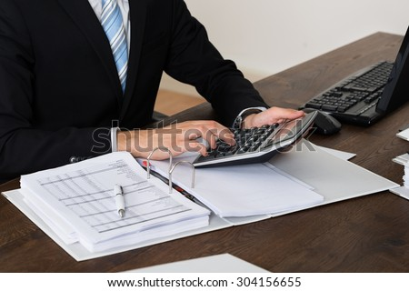 Close-up Of Businessperson Calculating Invoice Using Calculator In Office - stock photo