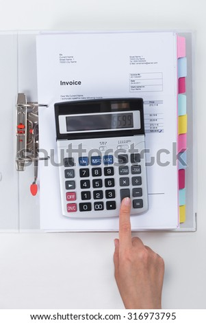 Close-up Of Businessperson Calculating Tax With Calculator At Desk - stock photo