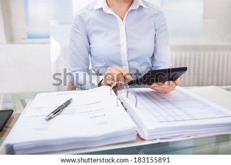 Close-up Of Businessperson Checking An Invoice On Calculator At Desk - stock photo