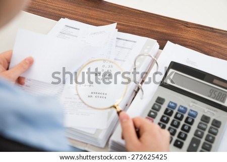Close-up Of Businessperson Examining Receipts With Magnifying Glass - stock photo