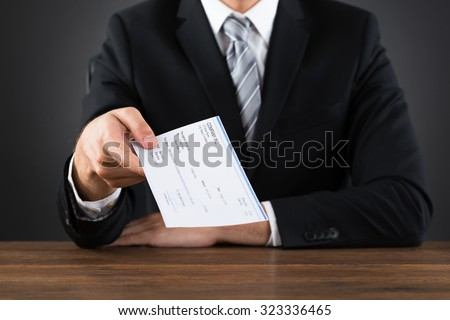 Close-up Of Businessperson Giving Cheque At Wooden Desk - stock photo