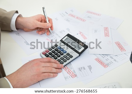 Close-up Of Businessperson Hand Calculating Bills At Desk - stock photo