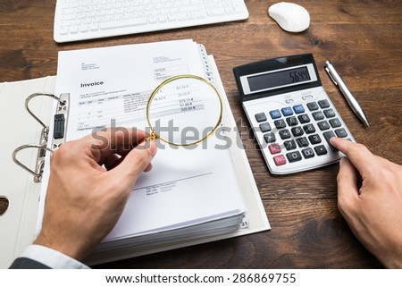 Close-up Of Businessperson Hand Examining Bills With Magnifying Glass At Desk - stock photo